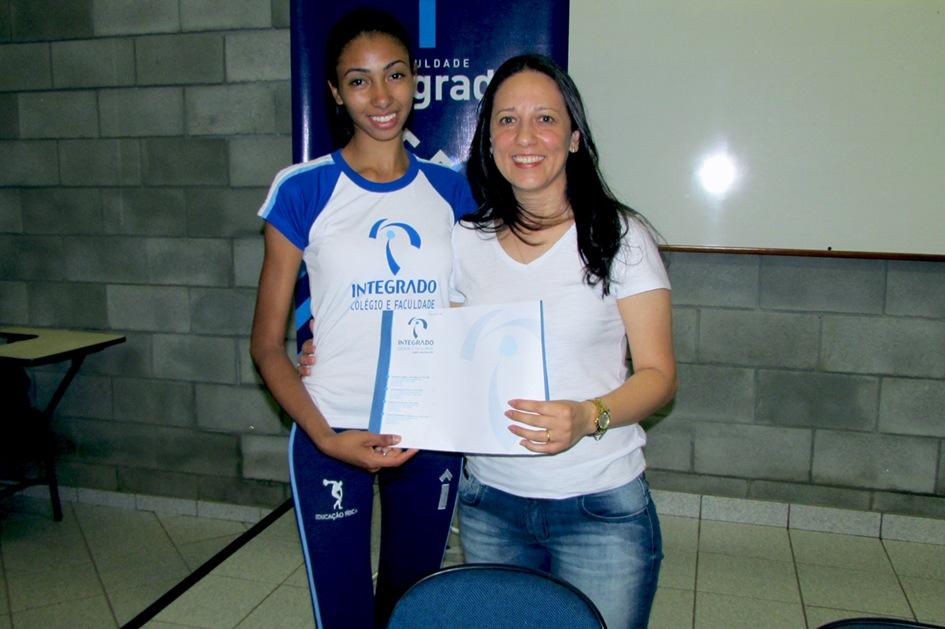 Acadêmica entrega certificado de participação à convidada Luciane Luz