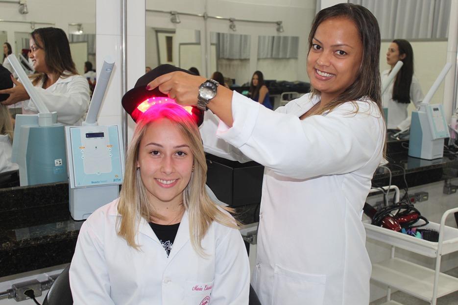 Acadêmicas utilizando o boné de fototerapia capilar